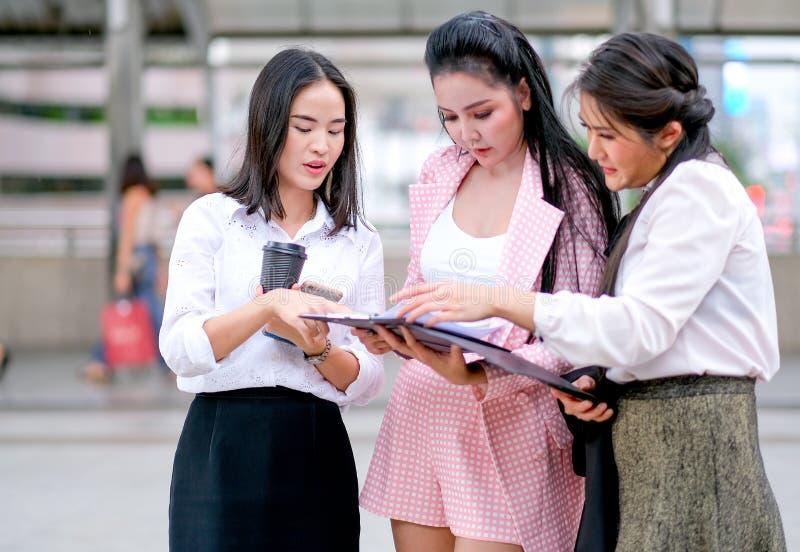 Drie bedrijfs Aziatische meisjes bespreken samen over hun werken buiten het bureau tijdens dagtijd royalty-vrije stock foto's