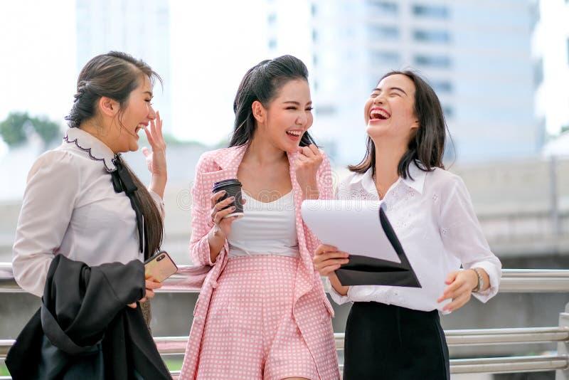 Drie bedrijfs Aziatische meisjes handelen als gelukkig en wekken buiten het bureau op tijdens dagtijd stock fotografie
