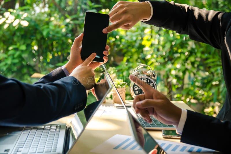 Drie bedrijfsmensen bespreken de bedrijfszaak op mobiele telefoon Ge?soleerd op wit royalty-vrije stock fotografie