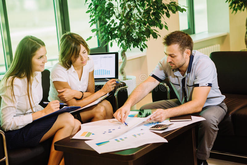 Drie bedrijfsmensen die op de omslagen van de bankholding zitten en gesprek hebben stock foto