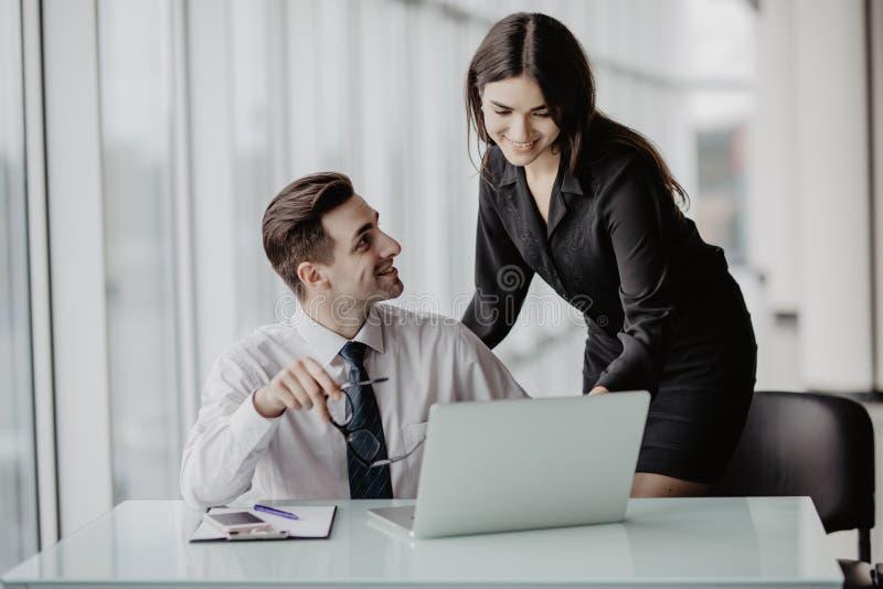 Drie bedrijfsmensen die op kantoor met administratie werken die laptop in bureau met behulp van royalty-vrije stock afbeelding