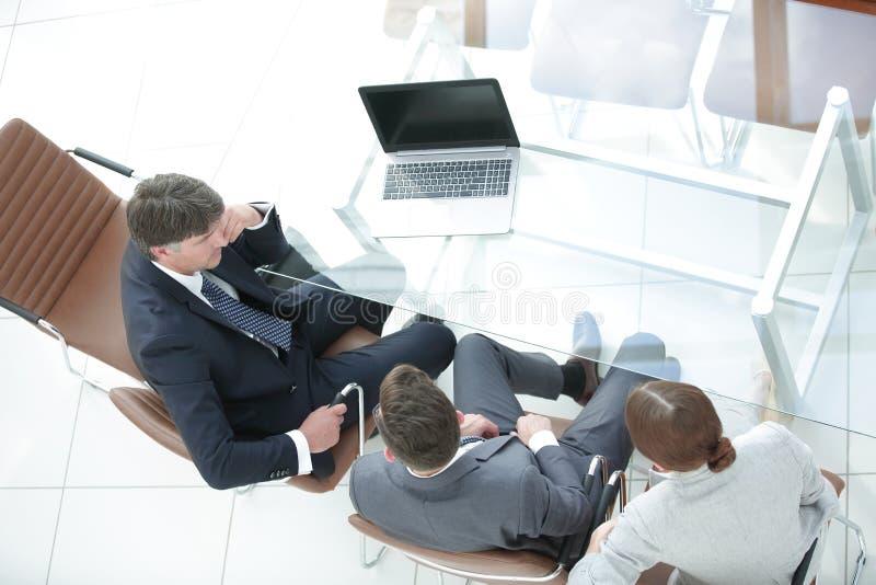 Drie bedrijfsmensen, die rond een bestuurskamerlijst samenkomen stock foto