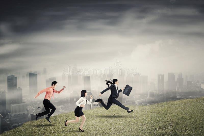Drie bedrijfsmensen die snelheid op de heuvel in werking stellen stock foto's