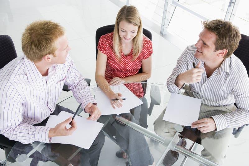 Drie bedrijfsmensen in een bestuurskamer stock afbeelding