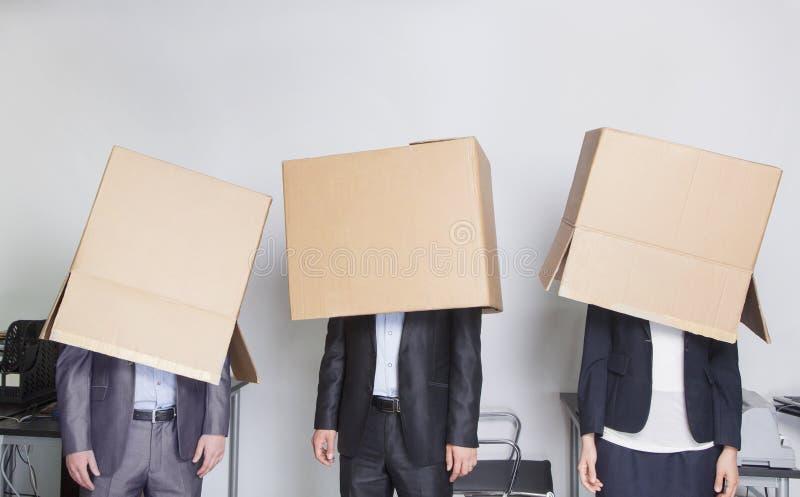Drie bedrijfsmensen met dozen over hun hoofden in een bureau royalty-vrije stock afbeeldingen