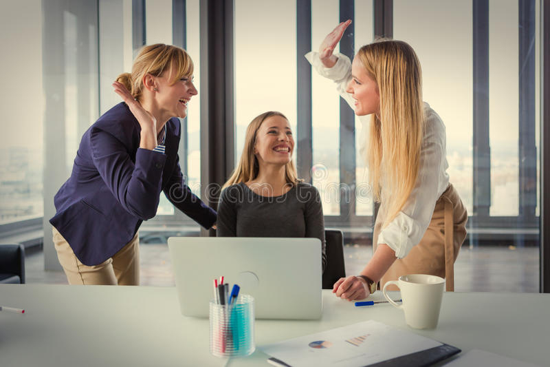 Drie bedrijfsvrouwen die in modern bureau goede projectresultaten vieren stock afbeelding