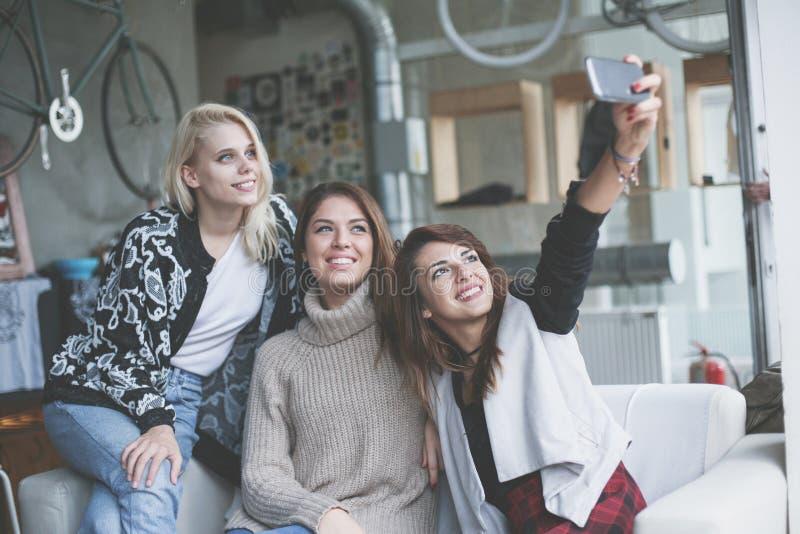 Drie beste vrienden in een koffie Jong meisje die zelf-beeld maken van royalty-vrije stock afbeelding