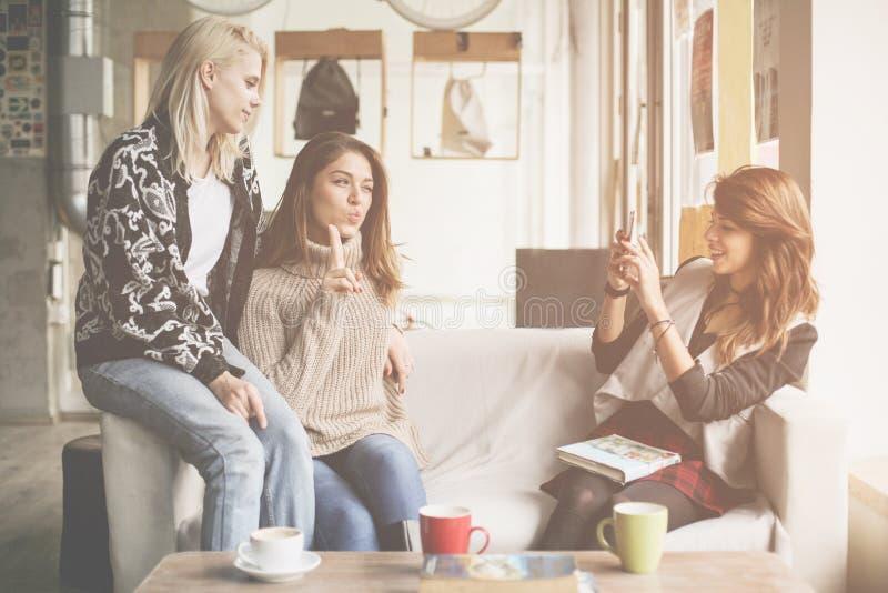 Drie beste vrienden in een koffie Jong meisje die zelf-beeld maken van royalty-vrije stock foto's