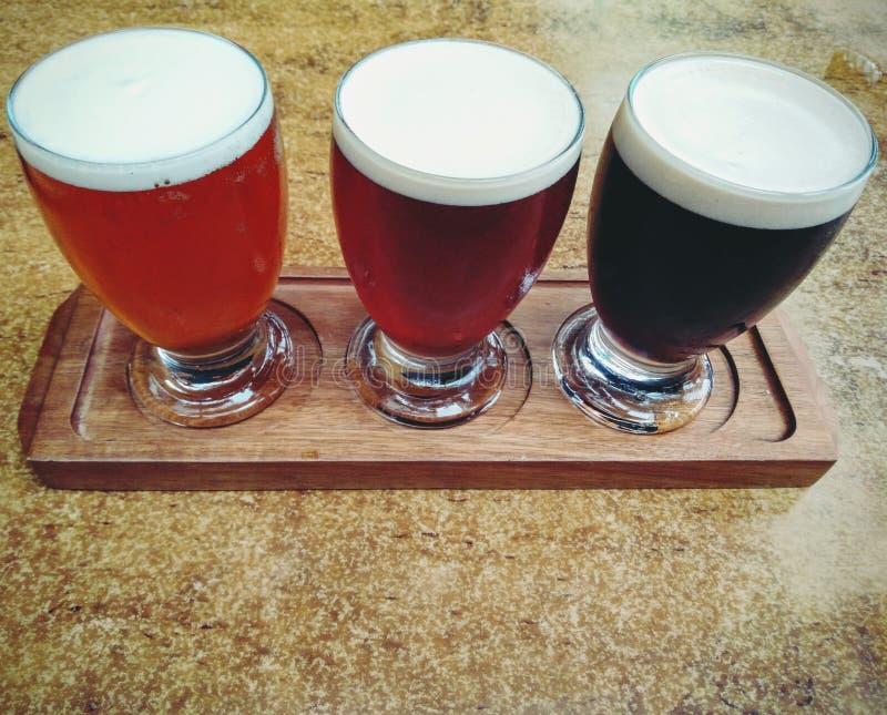 Drie bieren op een houten dienblad stock foto's