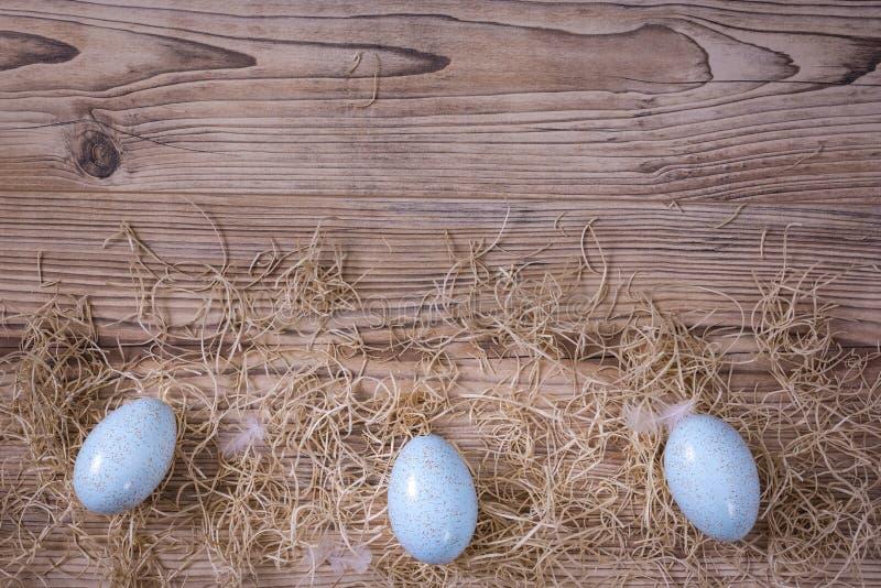 Drie blauwe eieren met veren en stro stock fotografie