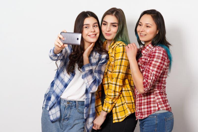 Drie blije meisjesmeisjes doen selfie Het glimlachen Op witte achtergrond stock foto