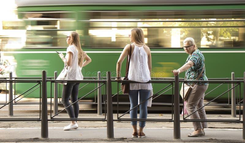 Drie blonde vrouwen die zich bij een bushalte bevinden en op publi wachten royalty-vrije stock fotografie