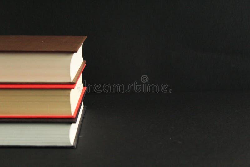 Drie boeken in hard dekkingsfragment, zwarte achtergrond, sluiten omhoog, vooraanzicht, vrije exemplaarruimte royalty-vrije stock foto