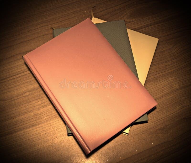 Download Drie Boeken Op Een Houten Lijst Stock Foto - Afbeelding bestaande uit achtergrond, patroon: 54085482