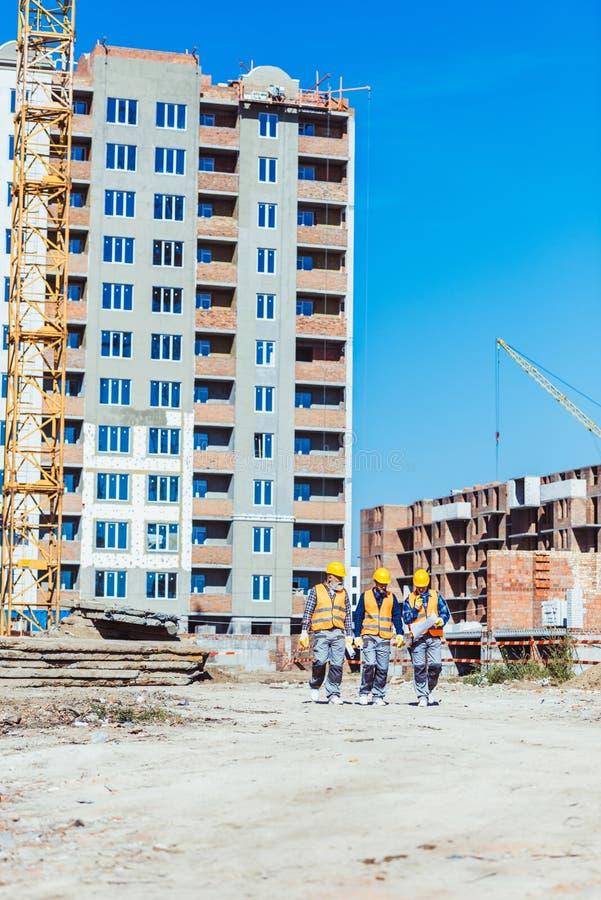 Drie bouwers in bouwvakkers en vesten die naar camera lopen stock afbeelding