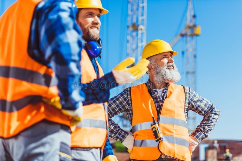 Drie bouwers in weerspiegelende vesten en bouwvakkers die het werk bespreken royalty-vrije stock afbeeldingen