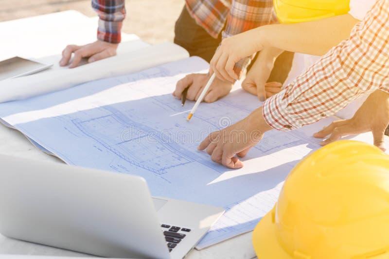 Drie bouwingenieurs die in openlucht in bouwsi werken royalty-vrije stock afbeeldingen