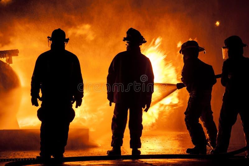 Drie brandweerlieden in eenvormig bestrijdend een brand stock afbeelding