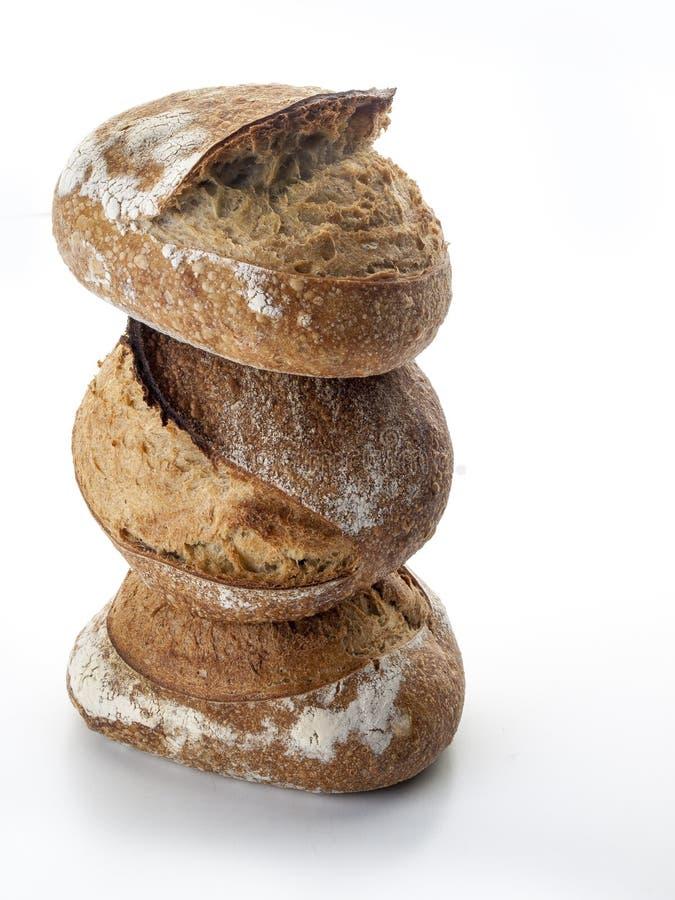 Drie broden van artisanaal die brood op een witte achtergrond worden gestapeld stock foto's