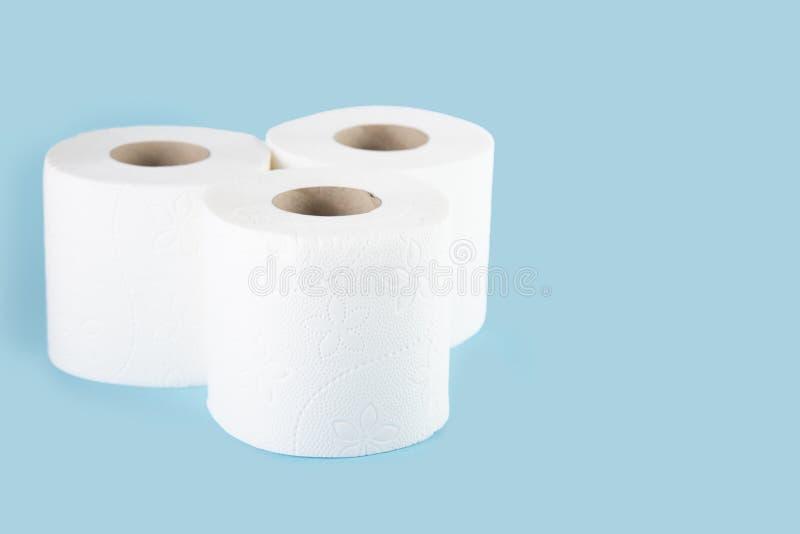 Drie broodjes van wit toiletpapier op een gekleurde achtergrond stock afbeelding