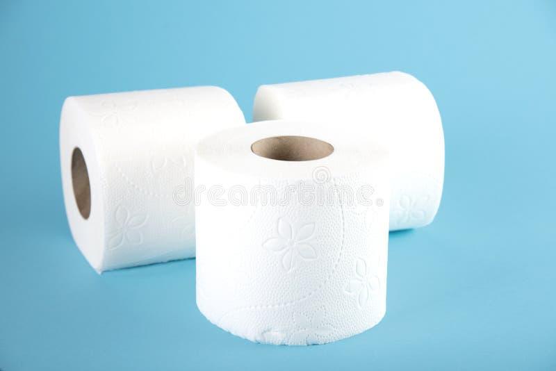 Drie broodjes van wit toiletpapier op een gekleurde achtergrond stock afbeeldingen