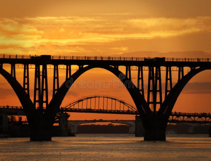 Drie bruggen op de rivier bij zonsondergang stock fotografie