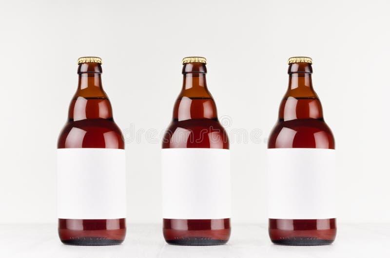 Drie bruine Belgische flessen van het steiniebier 500ml met leeg wit etiket op witte houten raad, bespotten omhoog stock fotografie
