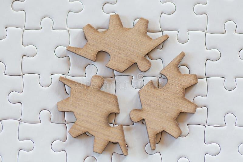 Drie bruine stukken van raadsel op een witte figuurzaagachtergrond, laatste stuk van puzzel om de opdracht, Bedrijfsoplossingen t stock foto's