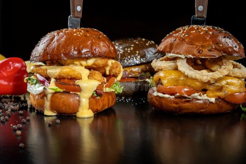 Drie burgers met uitsteeksels, uiringen, rundvleeskotelet en kip goudklompje-2 stock afbeelding