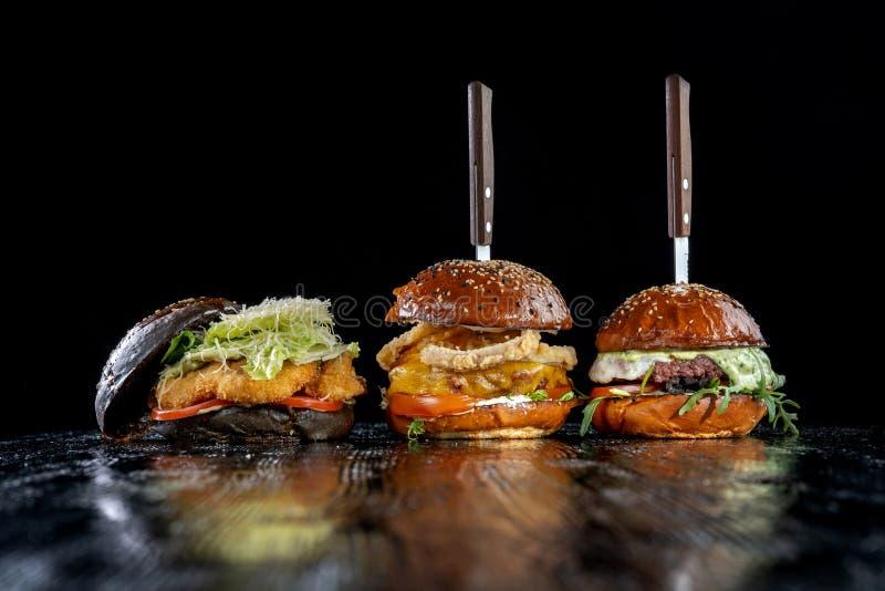 Drie burgers met vlees, uiringen, rundvleespasteitje en kippengoudklompjes stock foto