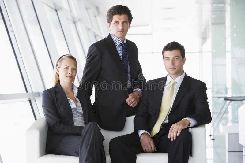 Drie businesspeoplezitting in bureauhal royalty-vrije stock foto