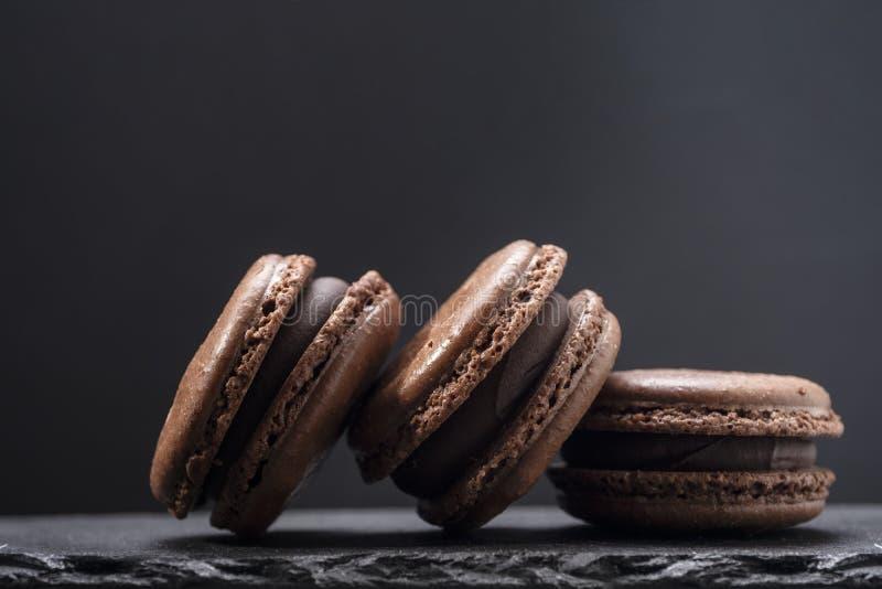 Drie chocolademakarons sluiten omhoog op donkere achtergrond stock afbeelding