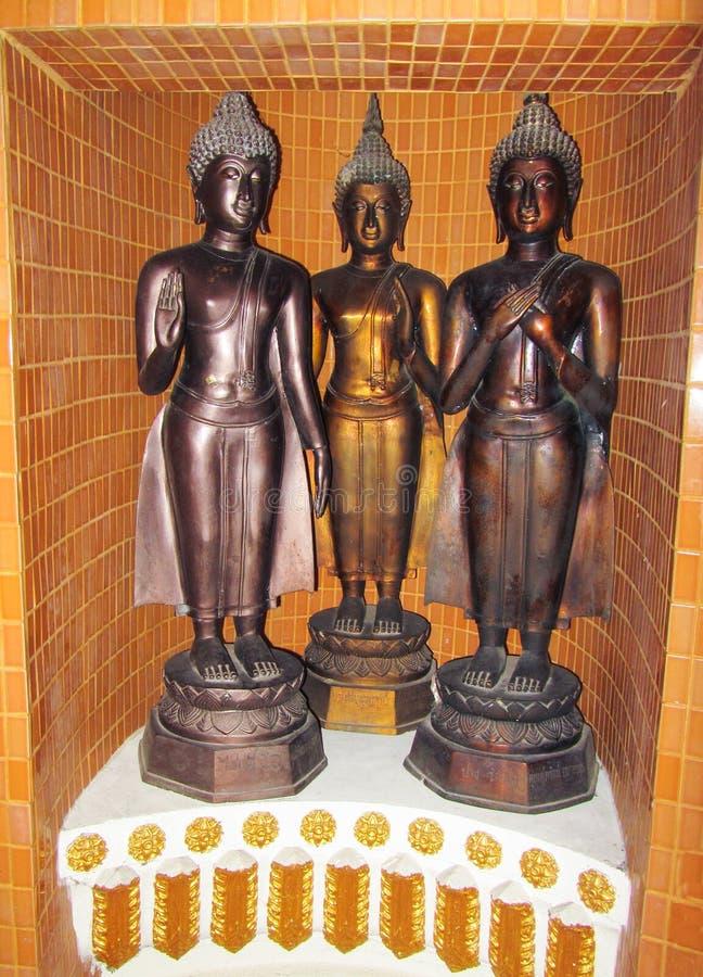 Drie cijfers van een brons Boedha die zich op een voetstuk op een gebied bevinden maakten met oranje keramische tegels in orde royalty-vrije stock foto's