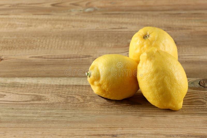 Drie citroenen op een houten lijst met exemplaarruimte voor uw tekst stock fotografie