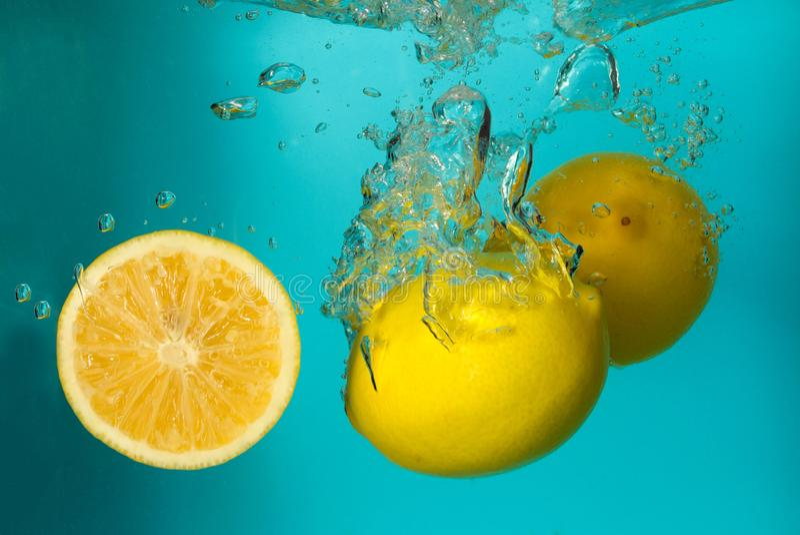 Drie citroenen spash in water op blauw royalty-vrije stock foto