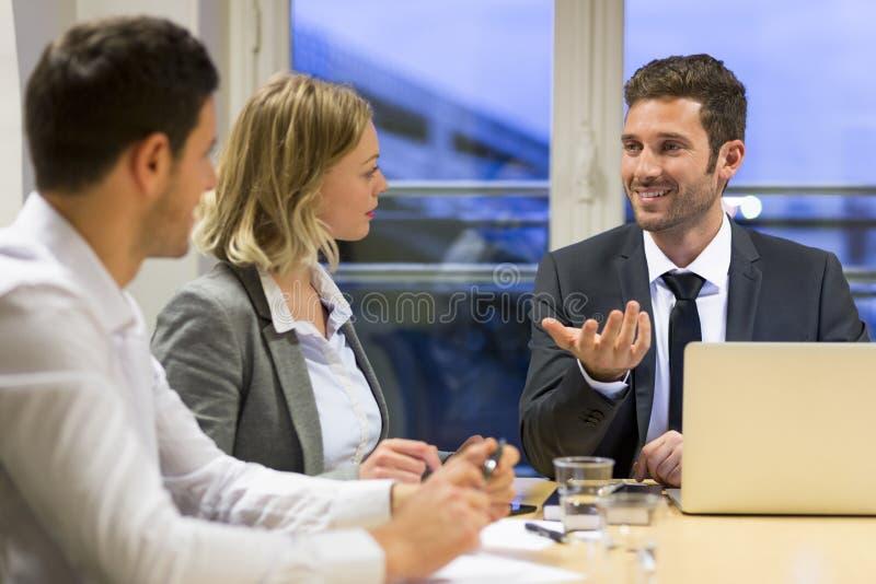 Drie commerciële volkeren die in vergaderzaal samenwerken stock afbeelding