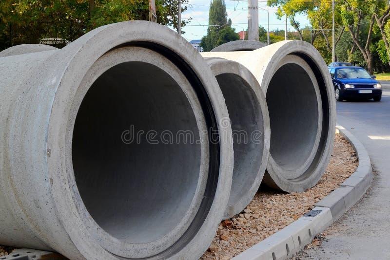 Drie concrete pijpen liggen op de onvolledige stoep dichtbij de weg bij de plaats van de wegenbouwwerken in de stad royalty-vrije stock foto's