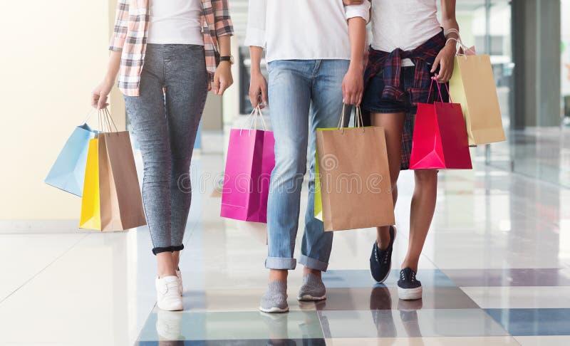 Drie consumenten met papieren zakken in winkelcentrum stock afbeeldingen