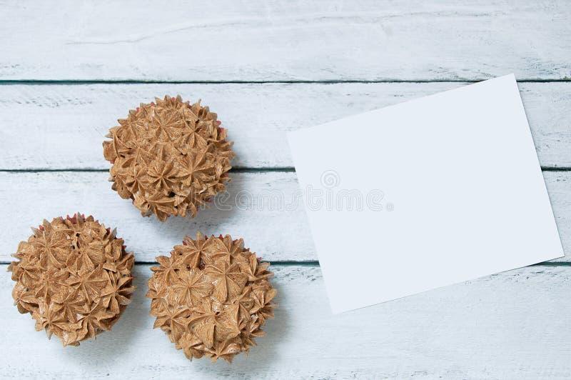 Drie cupcakes met chocoladeroom en een witte kaart royalty-vrije stock foto's