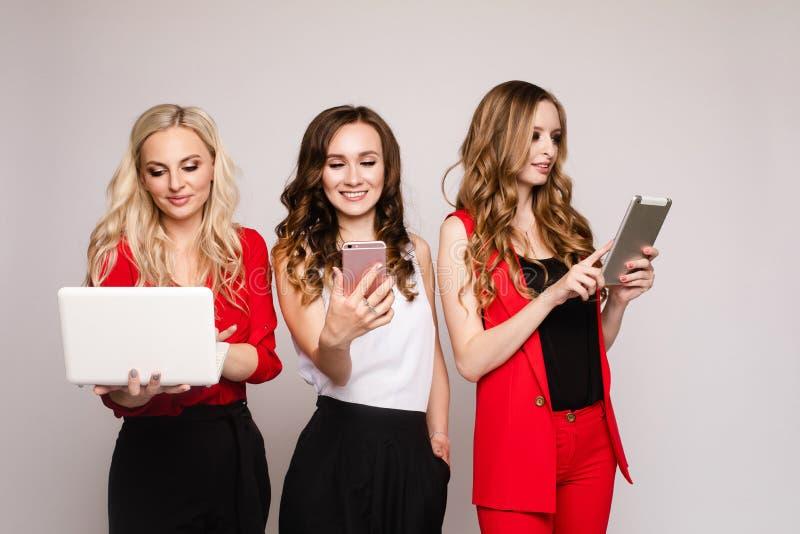 Drie dames die gadgets gebruiken Drie schitterende elegante jonge vrouwen in toevallig kleden zich royalty-vrije stock foto