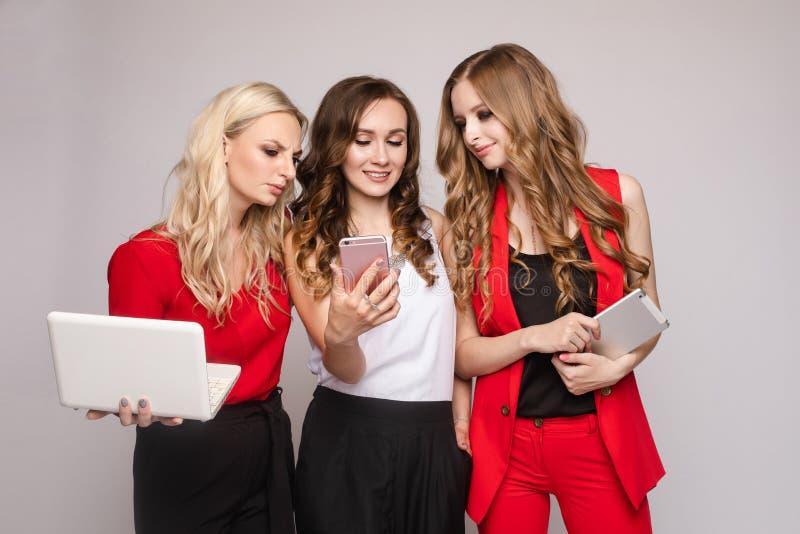 Drie dames die gadgets gebruiken Drie schitterende elegante jonge vrouwen in toevallig kleden zich stock foto