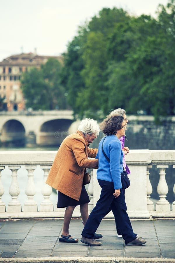 Drie dames die met bejaarden wandelen Openlucht, oudere zorg stock afbeelding