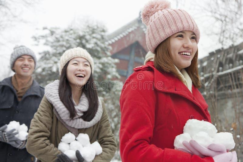 Drie de sneeuwballen van de vriendenholding in sneeuw in park royalty-vrije stock foto's
