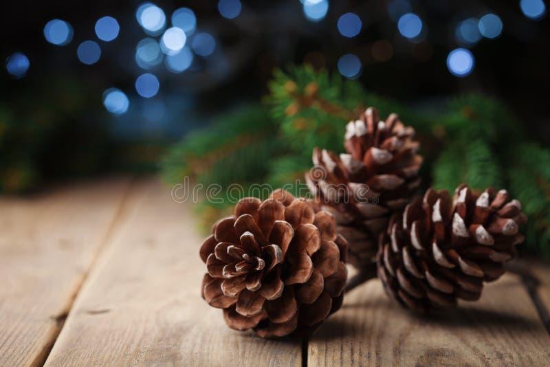 Drie denneappels en sparrentak op rustieke houten lijst De kaart van de Kerstmisgroet met bokeh stock fotografie