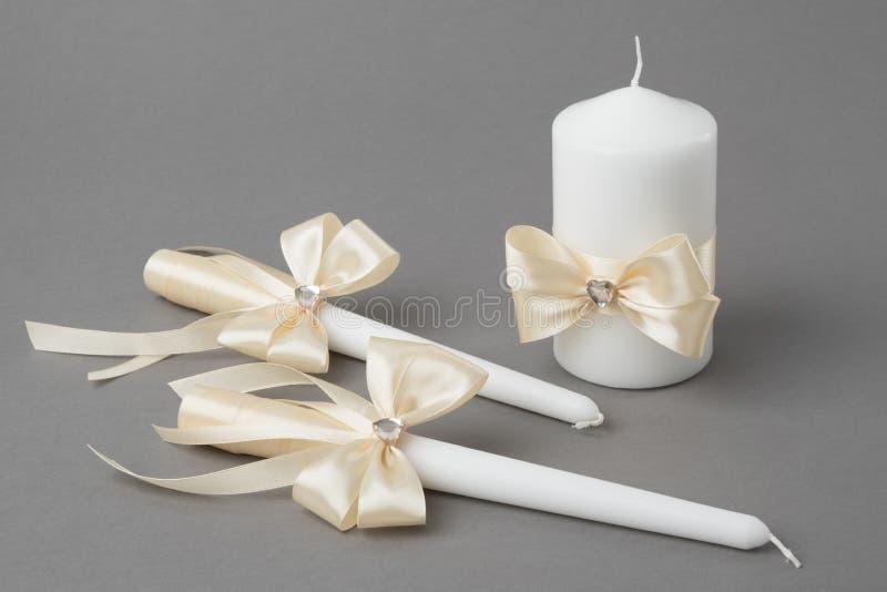 Drie die kaarsen met beige zijdebogen worden verfraaid op grijze achtergrond stock foto