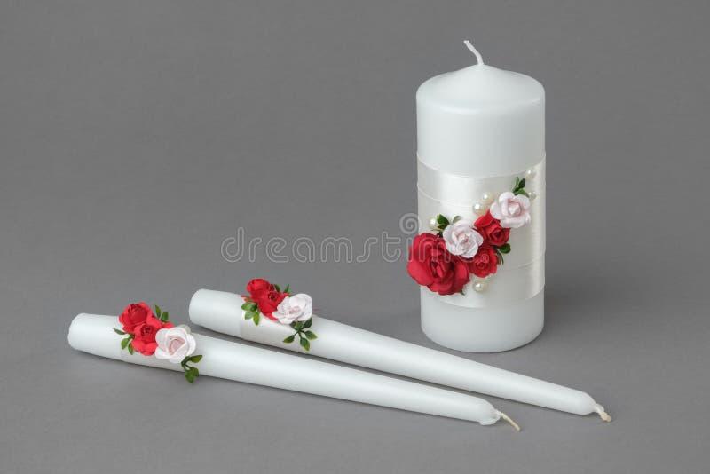 Drie die kaarsen met rode en roze rozen worden verfraaid royalty-vrije stock fotografie
