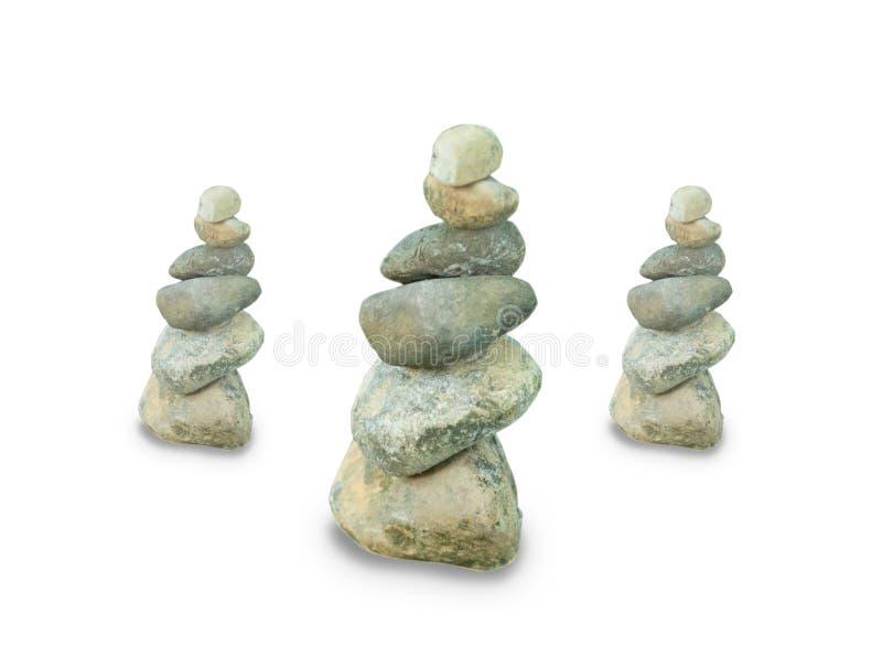 Drie die Kiezelsteentorens op witte achtergrond worden geïsoleerd Evenwichtige stenen in een stapel Drie stapels van rotsen stock foto