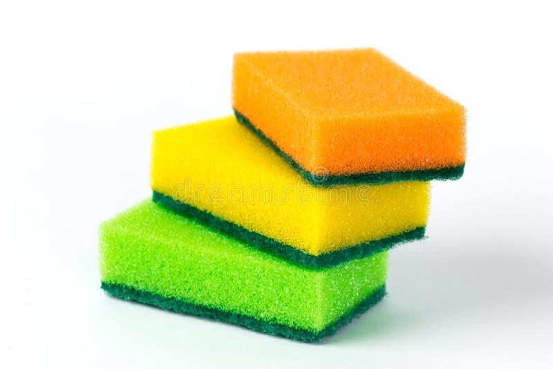 Drie die multi-colored sponsen voor wasschotels op witte achtergrond worden geïsoleerd stock foto's