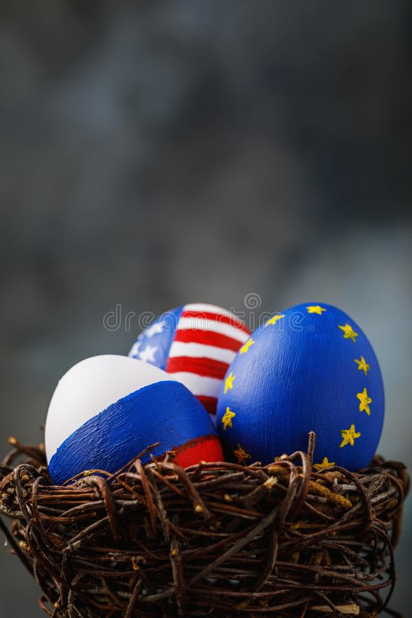 Drie die paaseieren in een nest in kleuren van de vlaggen van de Europese Unie van Rusland, van Amerika wordt geschilderd en stock foto