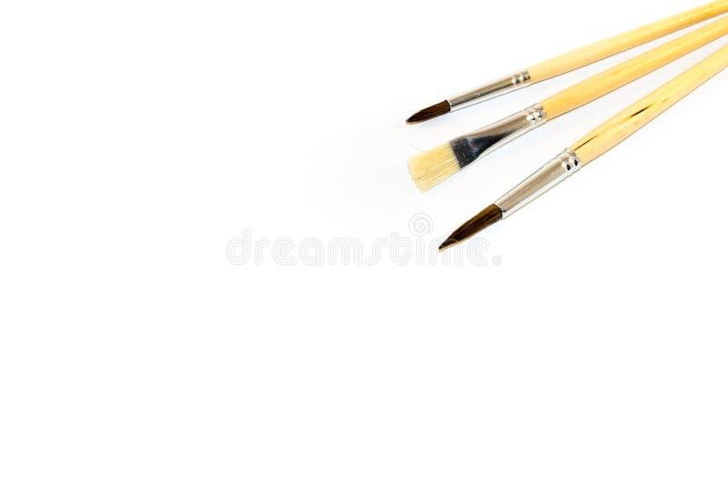 Drie die penselen op een witte achtergrond worden geïsoleerd royalty-vrije stock afbeelding